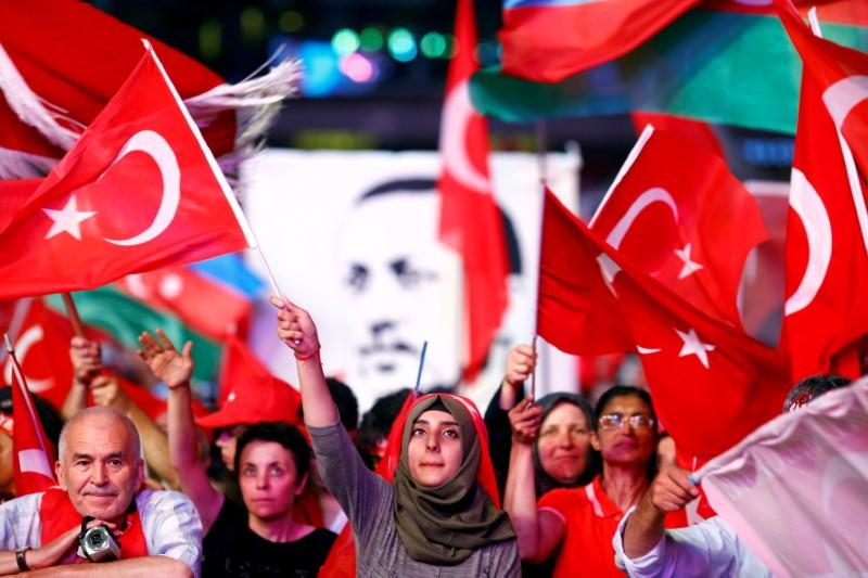 FILE PHOTO: Supporters of Turkish President Recep Tayyip Erdogan wave national flags as they listen to him through a giant screen in Istanbul's Taksim Square, Turkey, August 10, 2016. REUTERS/Osman Orsal/File photo